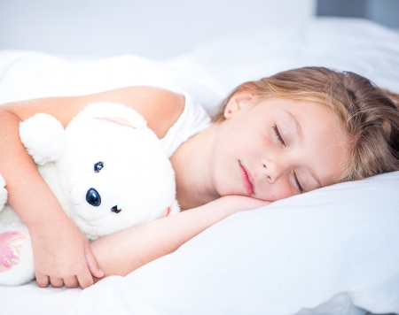 흰색 침대에서 어린 소녀의 자