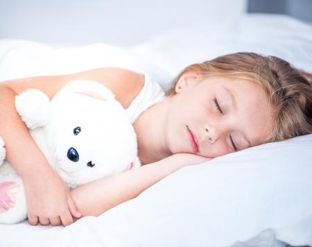 klein meisje slapen in het wit bed