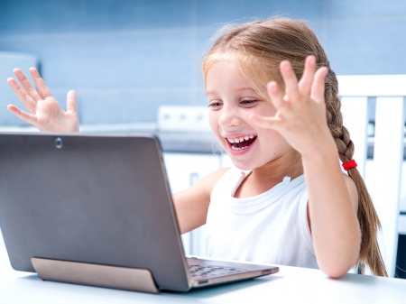 glad little girl with her computer at home at the table