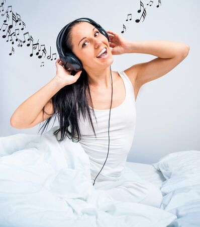 happy beautiful girl listening to music at home in white bed photo