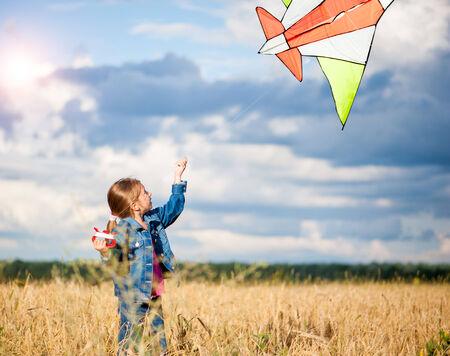 children running: cute little girl flies a kite in a field of wheat