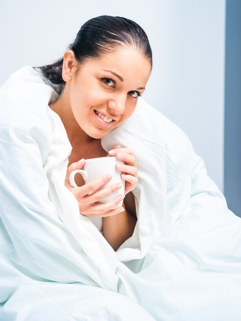 young woman drinking tea in bed at home Stock Photo - 22867150