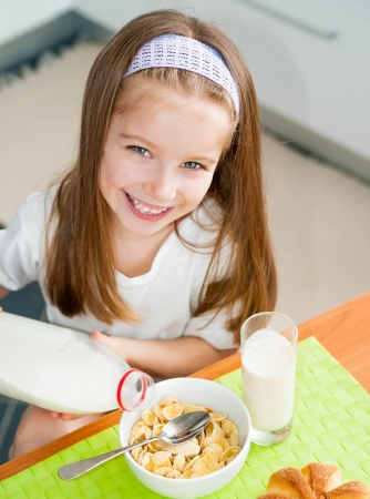 pours: smiling little girl pours milk in cereal