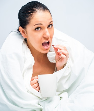 young woman drinking tea in bed at home photo