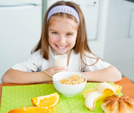 little table: little girl eating her breakfast at home