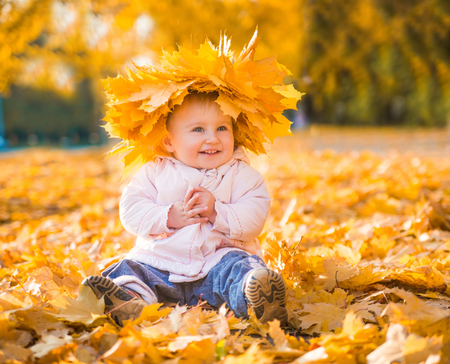 cheerful cute little girl among autumn maple leaves photo