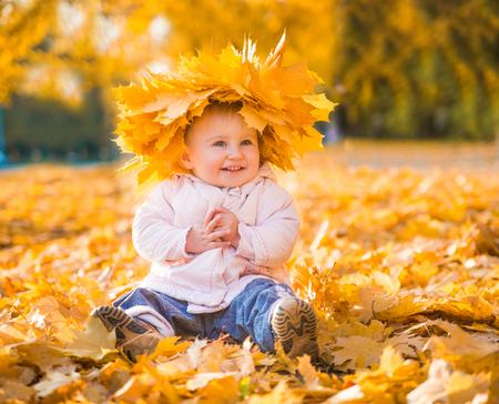 cheerful cute little girl among autumn maple leaves Stock Photo - 22936329