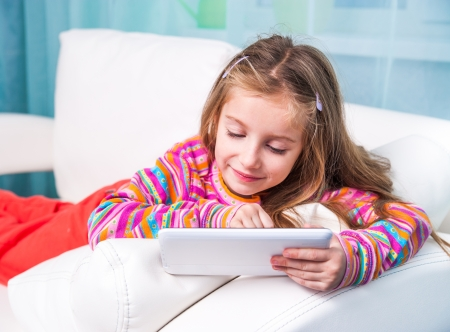 6 years girl: happy cute little girl with the tablet on a white sofa