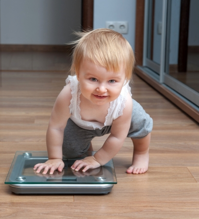 Cute baby check own weight on home scales