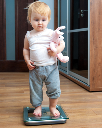 Cute baby with a toy check own weight on home scales photo
