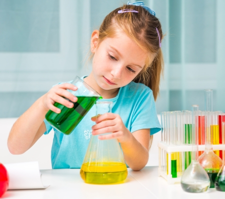 pretty little girl with flasks for chemistry photo