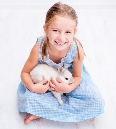 6 7 years: cute smiling girl in a blue dress with a white rabbit