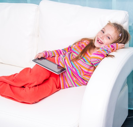 6 7 years: happy cute little girl with the tablet on a sofa at home