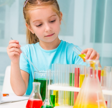 elementary age girl: cute little girl with flasks for chemistry