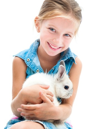 6 7 years: smiling little girl in denim clothing playing with white rabbit Stock Photo