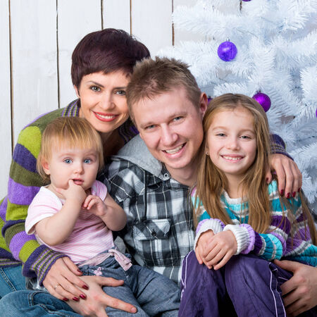 Christmas photo of a happy family around a decorated Christmas tree photo