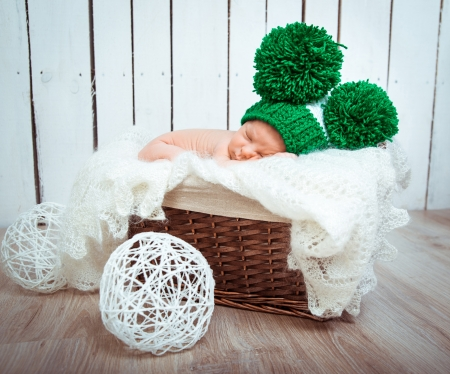 Cute newborn baby sleeps in a green hat photo
