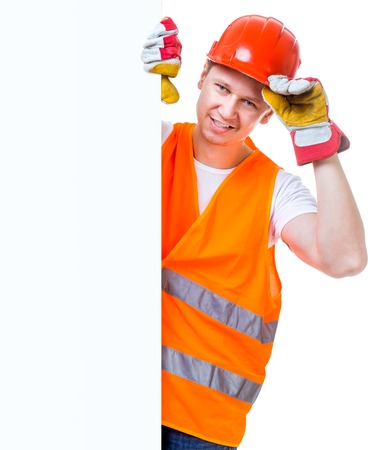 happy working man in a helmet holding a white blank with space for text photo