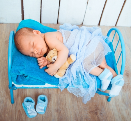 Cute newborn baby sleeps in a small bed with teddy bear photo