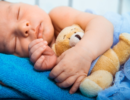 0 6 months: Cute newborn baby sleeps in a small bed with teddy bear closeup