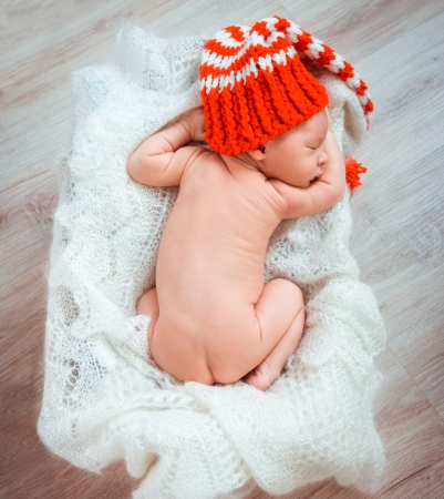 Cute newborn baby sleeps in a santa claus hat photo