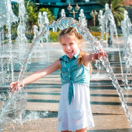 kleine niedliche Mädchen, die Spaß im Spritzer ein Brunnen