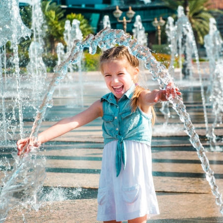 little cute girl having fun in splashes a fountain
