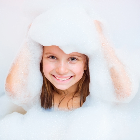 hair shampoo: Small happy girl is taking a bath with a foam