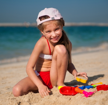 happy little girl on the beach playing in the sand photo