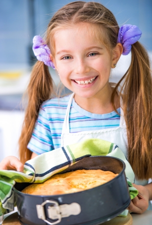 little cute girl showing apple pie that she baked photo