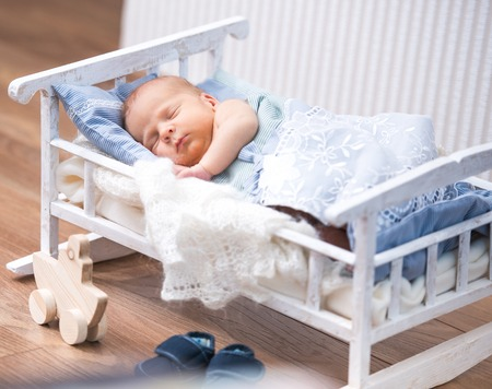 newborn boy sleeps in a small bed  nearby is a toy boat photo