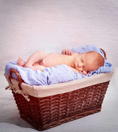cute newborn boy sleeping in a basket photo