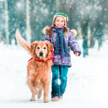beautiful little girl with her dog on the snow in winter photo