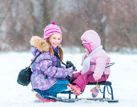 hfppy little girl photographed her sister sitting on a sled in the winter park photo