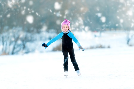 happy cute little girl in thermal suits skating outdoors photo