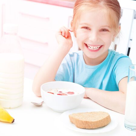 cute smiling little girl eating for breakfast muesli with strawberries photo