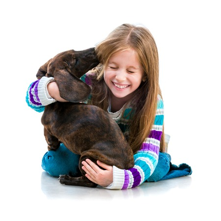 happy little girl with her dachshund in the studio on a white background photo