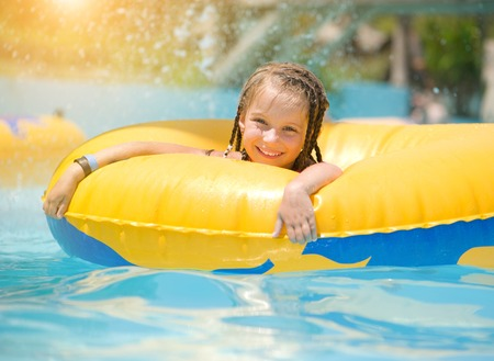 Cute little girl sitting on inflatable ring in swimming pool  photo