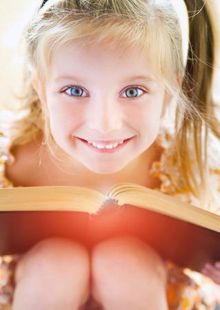 niños leyendo: dulce niña feliz leyendo un libro Foto de archivo