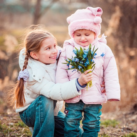 happy little girl and her sister holding a bouquet of snowdrops photo