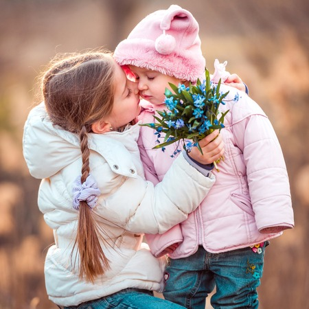 happy little girl kissing her sister and holding a bouquet of snowdrops photo