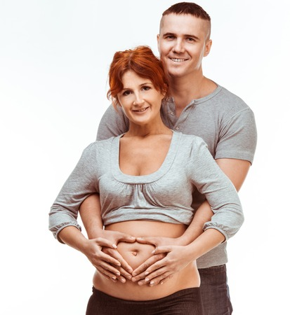 gestation: Young attractive couple  pregnant mother and happy father on a white background