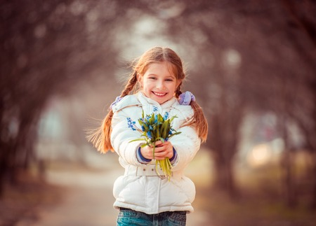 happy little girl smiling and holding a snowdrops photo