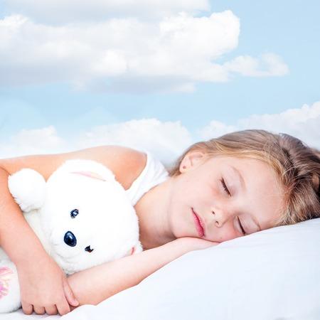 sono: doce menina dormindo em sua cama pequena Imagens