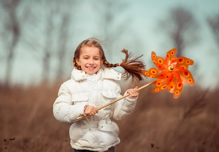 little girl in spring day holds windmill in hand photo
