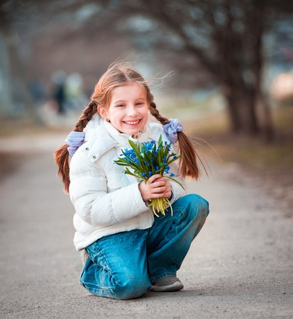 happy little girl smiling and holding a bouquet of snowdrops photo