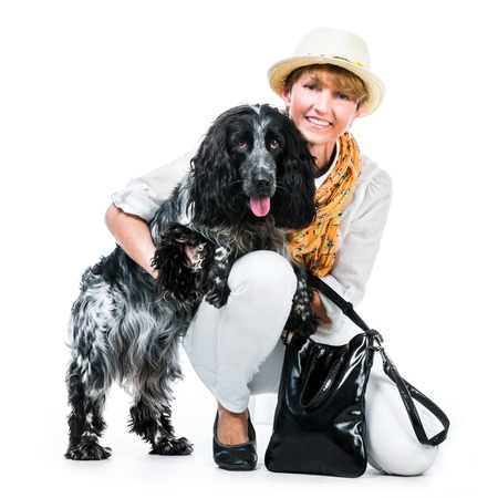 happy woman sit with her dog cocker spaniel in a studio isolated on white photo