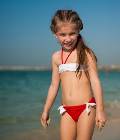 happy cute little girl in red-and-white swimsuit on the beach photo