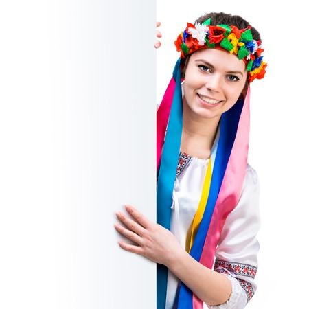 happy young women in the Ukrainian national costume behind white board photo