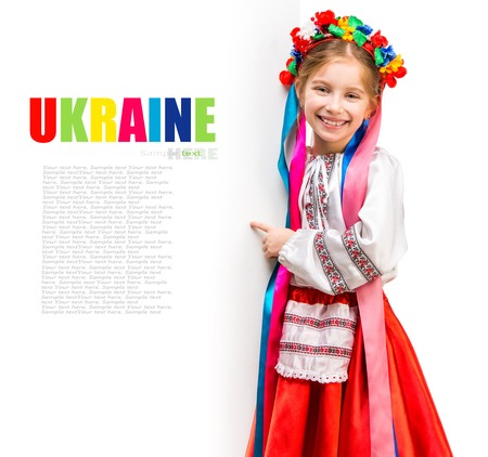 little girl in the Ukrainian national costume stand behind white board with space for text Stock Photo - 27351952